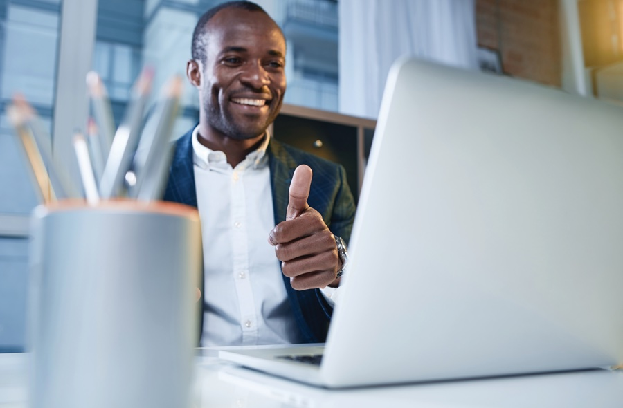 Guy at a desk giving thumbs-up sign