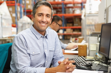 Smiling man sitting at a desk with hands folded