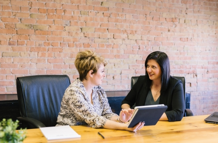 Two women have a conversation at a conference table in front of a brick wall.